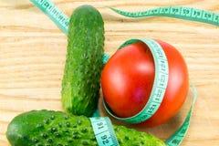 Gurka och tomat med att mäta Arkivfoto
