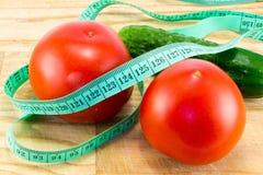 Gurka och tomat med att mäta Arkivbilder