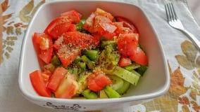 Gurka- och tomatsallad med svartpeppar och örter, i en vit keramisk bunke royaltyfri fotografi