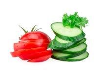 Gurka- och tomatskivor som isoleras på vit Arkivfoton