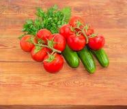 Gurken und Niederlassungen der roten Tomaten auf Holzoberfläche Stockbild