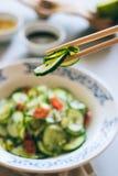 Gurkensalat in den chinesischen Essstäbchen Stockfoto
