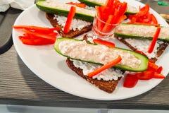 Gurkenschiffchen mit Frischquark, Paprikastreifen-auf Schwarzbro royalty-vrije stock foto