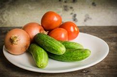 Gurkor med lökar och tomater Royaltyfria Bilder