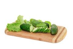 Gurkor och grön sallad som ligger på skärbräda Royaltyfria Bilder