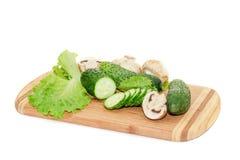 Gurkor och grön sallad som ligger på skärbräda Arkivfoton