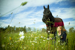 A gurl and her horse on a field royalty free stock photography