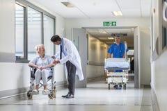 Υπομονετική νοσοκόμα διαδρόμων νοσοκομείων γιατρών που ωθεί το φορείο Gurney Στοκ εικόνα με δικαίωμα ελεύθερης χρήσης