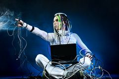 Guru. Shot of a futuristic young man sitting with a laptop and wires Royalty Free Stock Photo