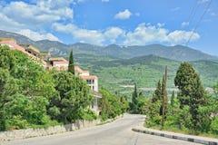 Gurzuf Road and Crimean Mountains with Cloudy Sky. GURZUF, CRIMEA - Beautiful spring Crimean landscape in Gurzuf with the view from Gurzufsskoye Shosse Gurzuf royalty free stock photos