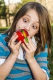Gusano del caramelo en manzana de las muchachas Imagen de archivo