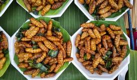Gusano picante frito en la hoja del plátano, bocado en Tailandia Foto de archivo libre de regalías
