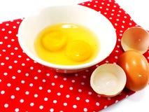 Gusci d'uovo rotti con i rossi d'uovo in ciotola ceramica sulla tovaglia rossa del pois Fotografia Stock