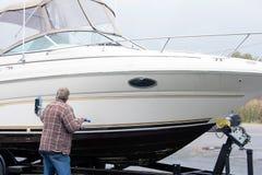 Guscio della barca di pulizia dell'uomo fotografia stock