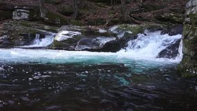 Gushing waterfall trips through rounded rock crevasses stock video