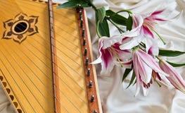 Gusli und rosa Lillies, die auf einem weißen Drapierung liegen lizenzfreie stockbilder