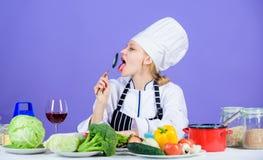 Gusto asombroso Delantal del sombrero del desgaste del cocinero de la mujer cerca de los ingredientes de la tabla El cocinero ado fotos de archivo libres de regalías