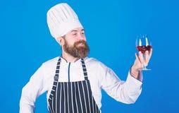 Gusto excelente Cocinero en sombrero y delantal del cocinero mejorar habilidad del sommelier Vino de servicio en el restaurante A imágenes de archivo libres de regalías
