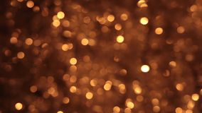 Gusty wind shakes bokeh from gold tinsel. Christmas background stock footage
