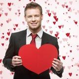 Gut aussehende Männer halten großes rotes Herz Stockfoto