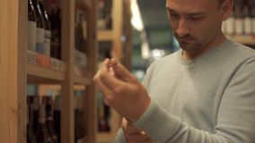 Gut aussehender Mann überprüft sorgfältig die Zusammensetzung auf dem Aufkleber einer Weißweinflasche im Spirituosenladen Weinfla stock video footage