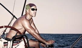 Gut aussehender Mann auf Segelboot stockfotografie
