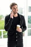 Gut aussehender Mann beim Telefonanruf, der Wegwerfschale hält Stockbild