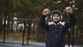Gut aussehender Mann in den Kopfhörern, die Übung ausdehnend während hörende Musik im Winterpark tun stock video