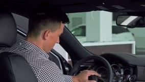 Gut aussehender Mann, der über seiner Schulter oben zeigt Daumen, sitzend in einem Neuwagen lächelt stock footage