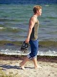 Gut aussehender Mann, der allein auf den Strand geht Stockbilder