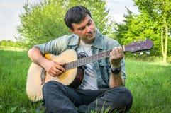 Gut aussehender Mann, der auf Akustikgitarre spielt Lizenzfreies Stockfoto