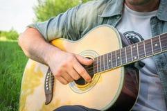 Gut aussehender Mann, der auf Akustikgitarre spielt Lizenzfreie Stockfotos