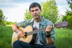 Gut aussehender Mann, der auf Akustikgitarre spielt Lizenzfreie Stockbilder