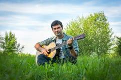 Gut aussehender Mann, der auf Akustikgitarre spielt Lizenzfreie Stockfotografie
