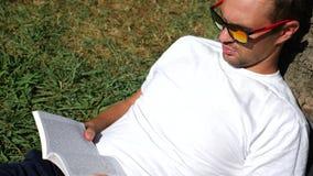 Gut aussehender Mann, der auf dem Gras im Park unter einem Baum, Lesebuch, 4k, Zeitlupe sitzt stock footage