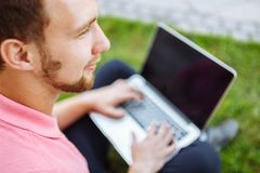 Gut aussehender Mann, der auf dem Gras in der Stadt mit einem Laptop, Jobsuche sitzt stockbilder