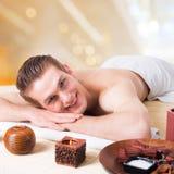 Gut aussehender Mann, der auf den Massageschreibtischen liegt Lizenzfreie Stockbilder