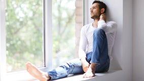 Gut aussehender Mann, der auf Fensterbrett, Fenster und das Träumen heraus schauend sitzt stock video