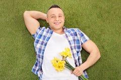 Gut aussehender Mann, der auf Gras liegt und Blumen hält Stockfotos