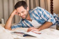 Gut aussehender Mann, der auf seiner Bettlesezeitschrift sich entspannt Stockfoto