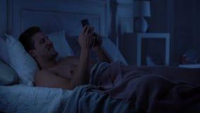 Gut aussehender Mann, der auf Smartphone flirtet und, plaudernd auf der Datierung des Standorts, Gerät lächelt stock video