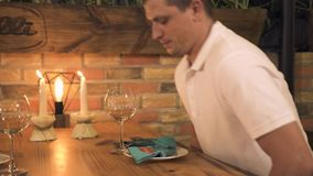 Gut aussehender Mann, der auf Tabelle mit brennenden Kerzen für romantisches Abendessen sitzt Wartefrau des jungen Mannes bei Tis stock video footage