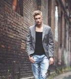 Gut aussehender Mann, der auf verlassenem Hintergrund steht Art und Weise Stockfoto