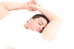 Gut aussehender Mann, der auf weichem weißem Kissen schläft Stockfotografie