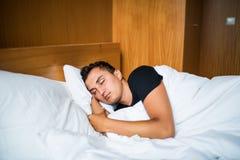 Gut aussehender Mann, der bequem in seinem Bett nachts schläft stockbilder