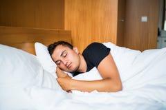 Gut aussehender Mann, der bequem in seinem Bett nachts schläft lizenzfreies stockbild
