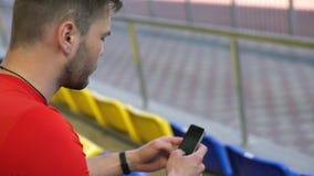 Gut aussehender Mann, der das Internet auf Smartphone auf einer Tribüne surft stock video footage