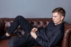 Gut aussehender Mann, der das schwarze Hemd sitzt auf dem ledernen Sofa tr?gt Komfort und Entspannung stockfotografie