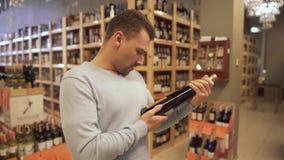 Gut aussehender Mann, der den Aufkleber auf der Weinflasche in einer Weinhandlung lernt Weinflaschen stehen auf hölzernen Regalen stock footage