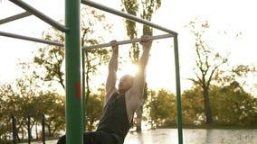 Gut aussehender Mann, der die Gymnastik draußen ausbildet auf horizontaler Stange hat Tut gymnastische Bremsungen auf der Querlat stock video footage